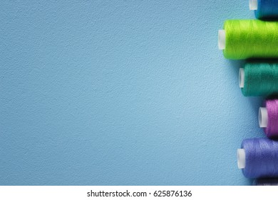 Set of colorful spools of thread on blue background. Mockup. Top view. Flat lay