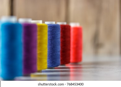 Set of colorful spools of thread on wooden background. Focus on blue spool