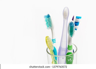 Set of colorful toothbrushes in glass on white background.