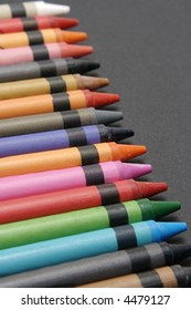 A set of colourful crayons against a black background.