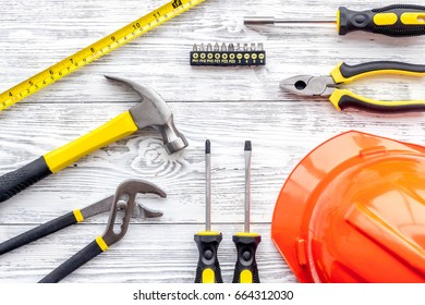 Set of construction tools on grey wooden desk background top view