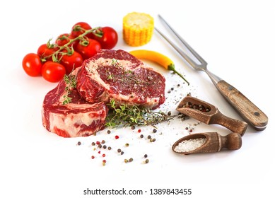 set for cooking a festive dinner for two. two raw marbled beef steaks, spices, vegetables and a grill pan with a meat fork. all on a white background