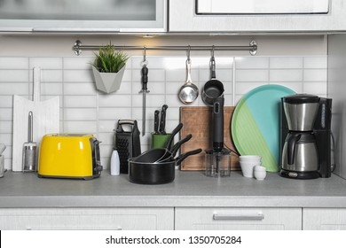 Set of cookware, clean dishes and appliances on kitchen counter