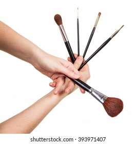 A set of cosmetic brushes in female hands isolated on white background.