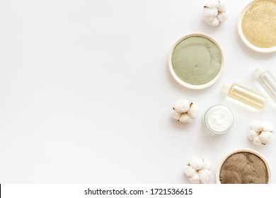 Set of cosmetic clays for facial beauty face mask on white table top-down frame space for text