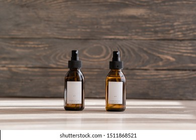 Set of cosmetic dark amber glass bottles with white labelson wooden background. Closeup, copyspace. Beauty blogging, salon treatment concept, minimalism brand packaging mock up