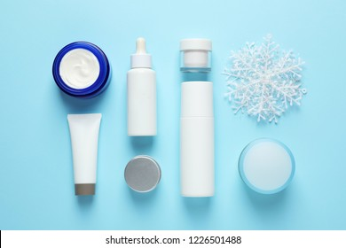 Set of cosmetic products on blue background, flat lay. Winter care