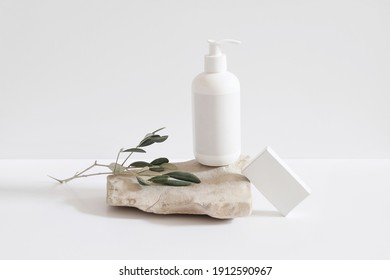 Set of cosmetic products on light background. White plastic pump bottle for shampoo, lotion mockup on stone podium. Blank soap box. Green olive tree branch. Healthy cosmetology, spa treatment concept.