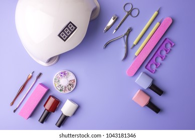 A set of cosmetic tools for manicure and pedicure on a purple background. Gel polishes, nail files and clippers, and the lamp top view. Composition for card with a place for text
