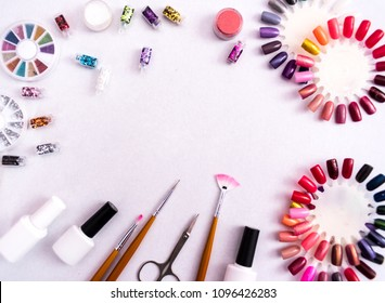 A set of cosmetic tools for manicure and pedicure on a weyt background. Gel polishes, nail files and clippers, and the lamp top view. Composition for card with a place for text