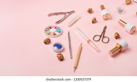 A set of cosmetic tools for manicure and pedicure on a pink background. Gel polishes, nail files and nippers and top view. Composition for a card with a place for the text, Flat-lay