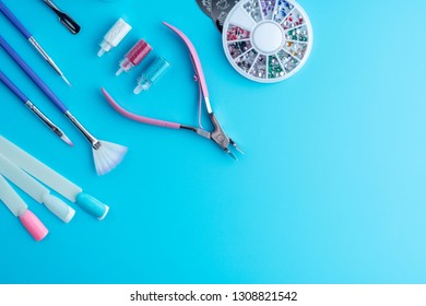 A set of cosmetic tools for professional manicure, nail care and to create beautiful designs on a blue background. Top view. Composition for card with a place for text
