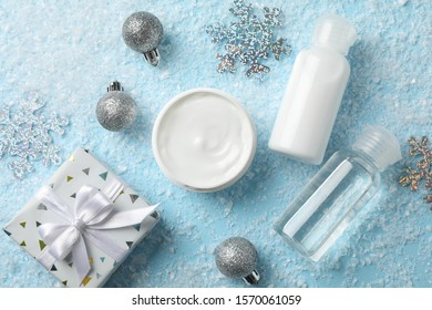 Set cosmetics, jar of winter cream for skin on snowy blue background, closeup. Top view