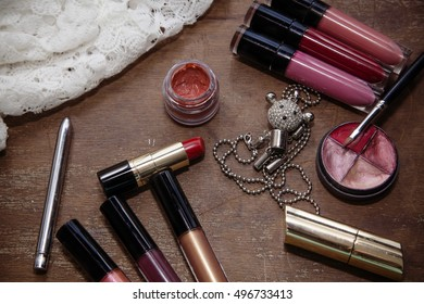 Set with Cosmetics on wood background, necklaces