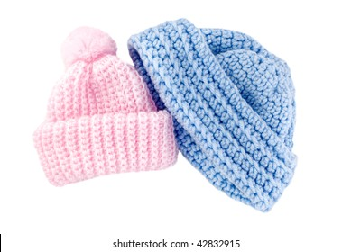 A set of crocheted pink and blue baby hats for boy and girl, isolated on white background, horizontal with copy space