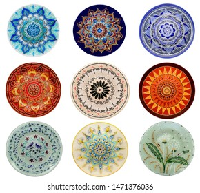 Set of decorative ceramic dishes hand-painted with acrylic paints floral pattern isolated on white background.