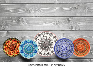 Set of decorative ceramic plates hand-painted dot pattern with acrylic paints on a gray wooden background. Copy space.
