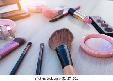 Set of decorative colorful cosmetics products and facial with blush, lipstick, mascara on brown wood table background.