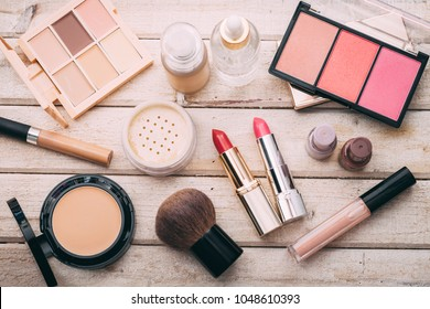 Set of decorative cosmetic. Face powder, concealer, eye shadow, blush, foundation. Wooden background.