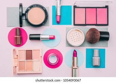 Set of decorative cosmetic. Face powder, concealer, blush, foundation, nailpolish, lipstics. Multicolored paper background.