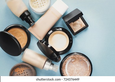 Set of decorative cosmetic. Foundations, facial powders. pastel colored. Blue background.