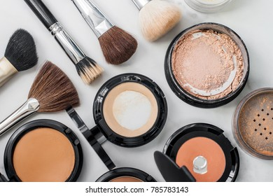 Set of decorative cosmetic. Make-up brushes different size and color. Face powders, blush, foundations. White background.