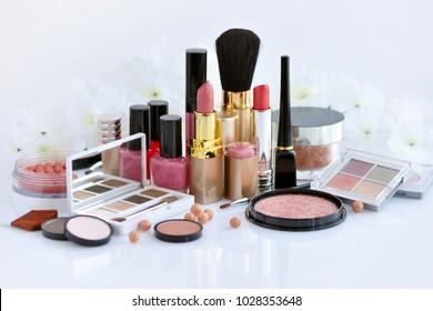 Kosmetikset für Dekoration: Puder, Lippenstifte, Bürste, Blüte, Auschatten, Nagellack auf weißem Hintergrund
