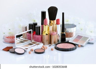 Set of decorative cosmetic: powder, lipsticks, brush, blush, eyeshadow, nail polish on a white background