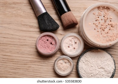 Set of decorative cosmetic powder, shimmer, eye shadow, blush and brushes on wooden background, beauty and makeup concept