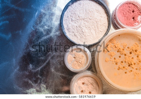 Set of decorative cosmetic. Powder, shimmer, eye shadow and blush on foil metallic background, beauty and makeup concept with copy space