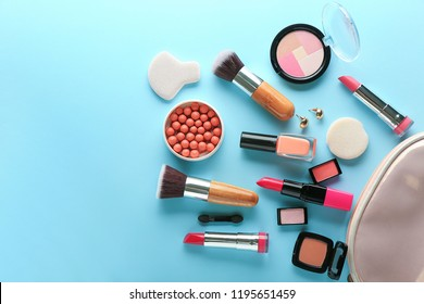 Set of decorative cosmetics with bag on color background