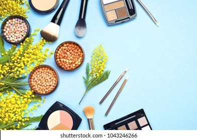 Set of decorative cosmetics for make-up Powder Rouge Eyeshadow Corrector Brushes and flowers of mimosa on blue background. Makeup Accessories Top view Flat Lay