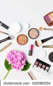 Set of decorative cosmetics mascara powder lipstick eyeshadow blush makeup brush pink hydrangea flowers on light background top view Flat lay copy space. Beauty blogger concept. Fashion background