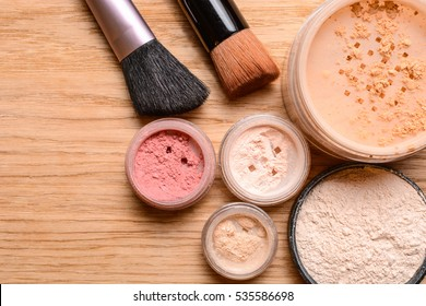Set of decorative cosmetics. Powder, shimmer, eye shadow, blush and brushes on wooden background, beauty and makeup concept