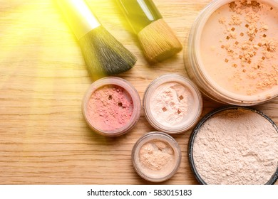 Set of decorative cosmetics. Powder, shimmer, eye shadow, blush and brushes on wooden background, beauty and makeup concept with sunlight