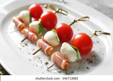 Set of delicious canapes on white plate closeup