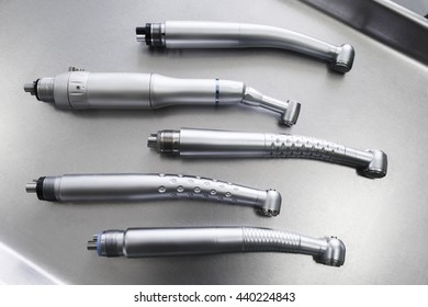 Set of dental turbine handpieces without burs flat lay. Top view on set of dental turbine handpieces on metal medical tray.
