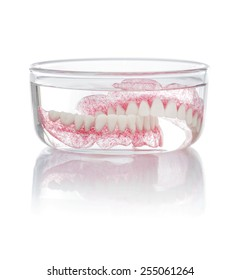 A Set of Dentures in A Glass of Water Isolated on White Background