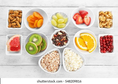 Set of diet products in saucers on wooden background
