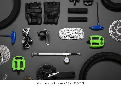Set of different bicycle tools and parts on grey background, flat lay