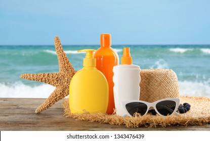 Set with different bottles of sun protection body cream and beach accessories on wooden table against seascape. Space for design