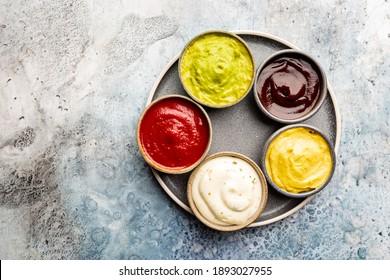 Set of different bowls of various dip sauces, top view
