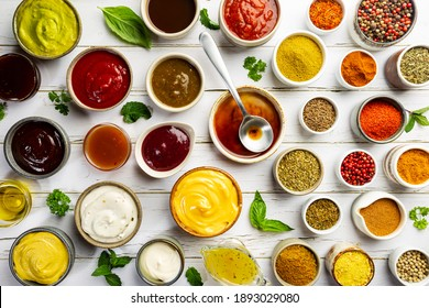 Set of different bowls of various dip sauces on white background, top view