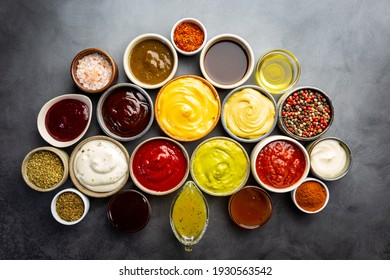Set of different bowls of various dip sauces, on dark background, top view