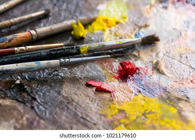 set of different brushes and oil paints to paint scattered on a dark wooden table top view