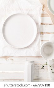Set of different ceramic plates and bowls styled on white distressed wooden background. Vertical composition. Flat lay with copy space
