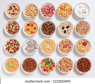 set of different cereals with milk on a white background. 20 bowls with cornflakes, kashi, cereals and berries. the concept of breakfast food. flat lay, top view