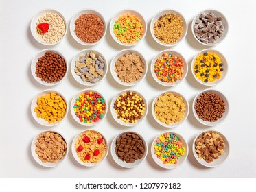set of different cereals on a white background. 20 bowls with cornflakes, kashi, cereals and berries. the concept of breakfast food. flat lay, top view