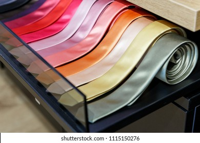 Set of different color skinny neckties on a shelf in a men clothing store