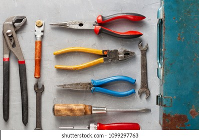 Set of different construction vintage tools and instruments for household with old iron box on gray concrete background. Fathers Day concept. Top view, copy space, flatlay